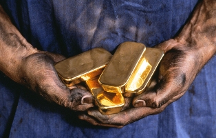 A man holding 4 gold bars in his hands