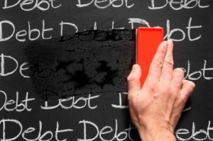 "An hand erasing the words ""debt"" written several times on a blackboard"