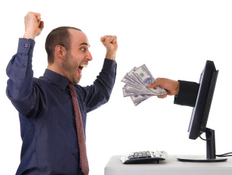 A man happy with money in front of a laptop