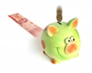 Coins into a green piggy bank