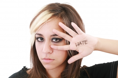 "Angry Teenager with ""hate"" word written below her hand"