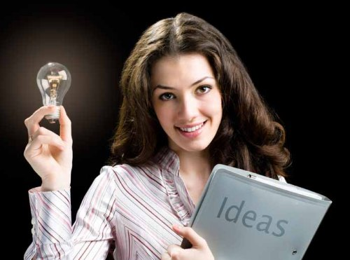"Girl with a bulb in her hands and a book with word ""ideas"" written on it"