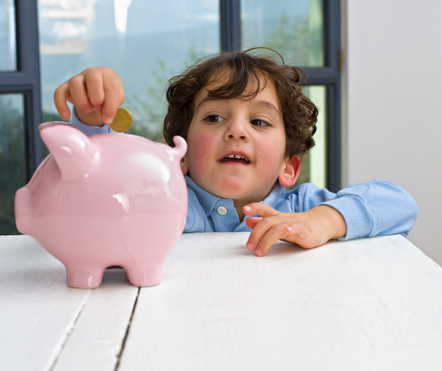 A kid filling a pig money box with a coin