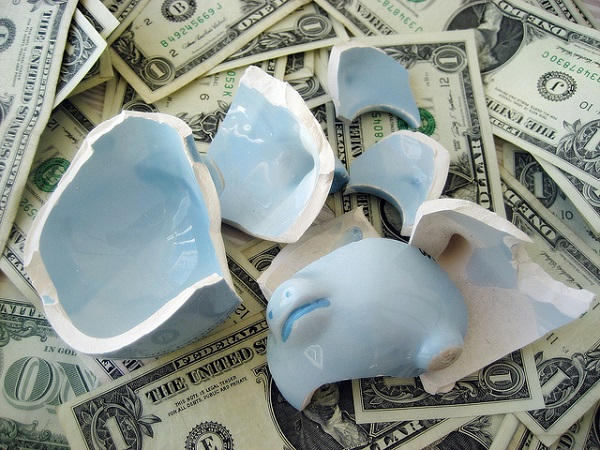 broken piggy bank with dollar banknotes below